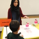 Dua Azhar shows off her scribbling robot. (Keyra Kristoffersen/City Journal)