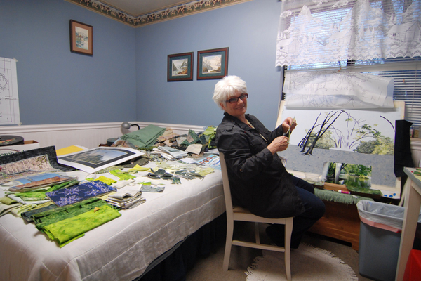 Mary Hutchings hand-cuts each half-inch piece to be applied as background foliage for her current project of the Susquehanna River in New York. (Keyra Kristoffersen/City Journals)