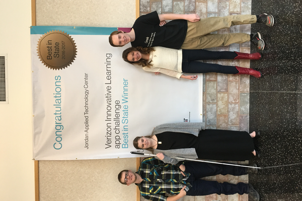 "Kyle Christensen, Brandee Hick, Taylor Dee and Eric Evans pose for a picture by the banner Verizon sent them for winning ""Best in State"" in an app challenge. (Tori La Rue/City Journals)"