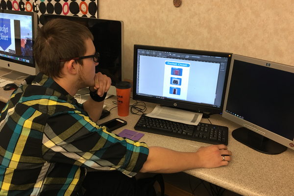 "Kyle Christensen, a senior in the web design program at the Jordan Applied Technology Center, looks over the app design he created with four other classmates. The app won ""Best in State"" in the Verizon Innovative Learning app challenge. (Tori La Rue/City Journals)"