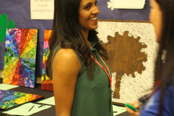 Event coordinator Sonal Kerr stands by her son's project during the silent auction. (Travis Barton/City Journals)