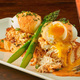 Crab Cake Benedict made from crabmeat, packed eggs, and asparagus set upon toasted focaccia and topped with cajun lobster sauce.
