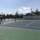 Redd Owen gets ready to return the tennis ball as Parker Watts watches. (Koster Kennard/ City Journals)