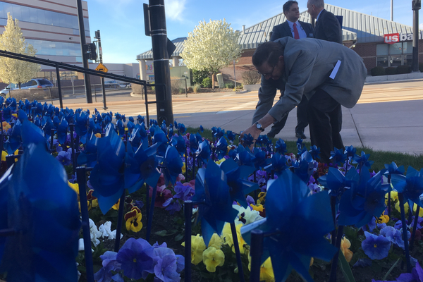 Councilman Don Christensen plants the last of his pinwheels in front of City Hall. Each pinwheel represents a victim of child abuse. (Travis Barton/City Journals)