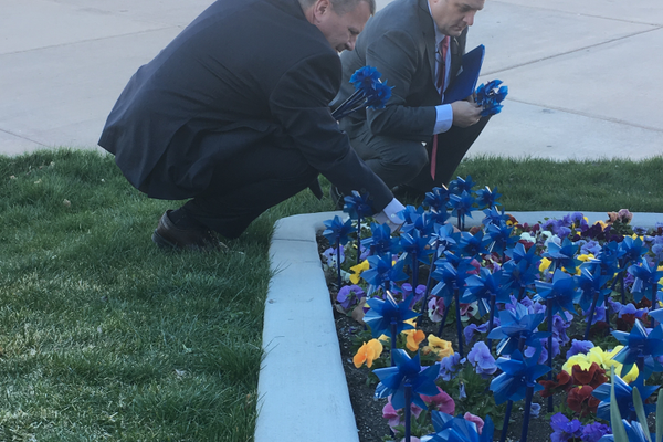 Councilman Steve Buhler (left) and Jeff Bird, Family Support Center executive director, plant pinwheels in front of City Hall. Each pinwheel represents a victim of child abuse. (Travis Barton/City Journals)