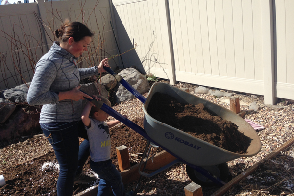 Enoch Oler helps his mom Sarah Oler add manure compost to their garden bed. (Natalie Conforto/City Journals)