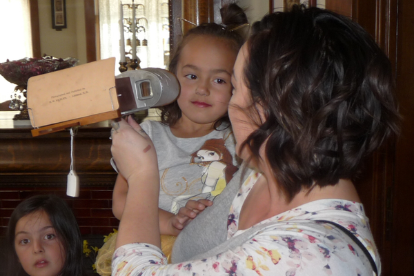 Tattianna Martin shows her daughter Olivia an antique stereoscope card viewer. (Carl Fauver/City Journals)