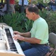 Sam Melonas, KidsEat! board member, played the piano and sang during the garden tea party. (Travis Barton/City Journals)