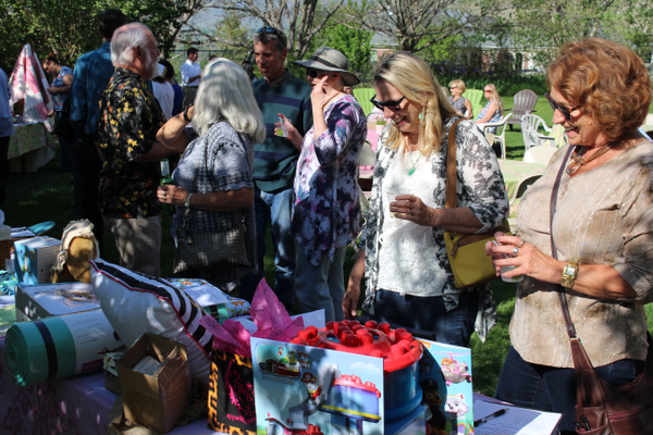 Attendees look over the silent auction items during the Help Us Bloom event. (Travis Barton/City Journals)