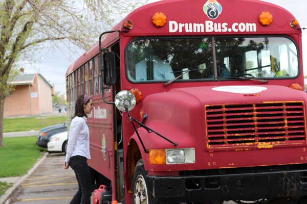 Heather Buhler, a Salt Lake County librarian, boards Nels Anderson's DrumBus during a Kearns Library activity. Anderson taught Buhler and others how to play djembe drums. (Tori La Rue/City Journals)