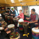 """Nels Anderson, wearing the green hat, teaches community members how to play djembe drums. Anderson brought his """"mobile music room"""" DrumBus to the Kearns Library on April 24. (Tori La Rue/City Journals)"""