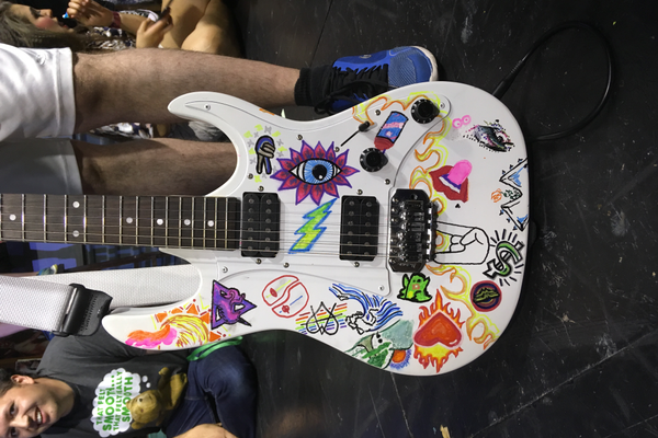The guitar used by Eric Williams during the musical, decorated with signatures and drawings from the cast. (Travis Barton/City Journals)