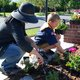 Paige Brown shows Will Dummer how to plant new flowers at the Sandy Museum. (Keyra Kristoffersen/City Journals)