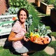 Pat Thomas, founder of Backyard GardenShare, holds a tub of produce next to her garden. Thomas has a master's degree from Westminster in arts and community leadership. (Allan Thomas/Backyard GardenShare)