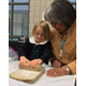 Through the Adopt-a-Native-Elder program, St. John the Baptist students learned how to grind wheat with a stone. (Tina Fields/St. John the Baptist)