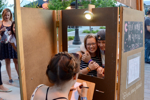 Fifteen-year-olds Bethany and Abbie pose for Natalie Allsup-Edwards as she hand draws the pair at her photo booth for the Blue Moon Festival. (Lexi Peery/City Journals)