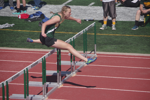 Madeline Martin leaps over a hurdle. Martin had two of the fastest hurdle times in the state this past spring. (Julie Slama/City Journals)