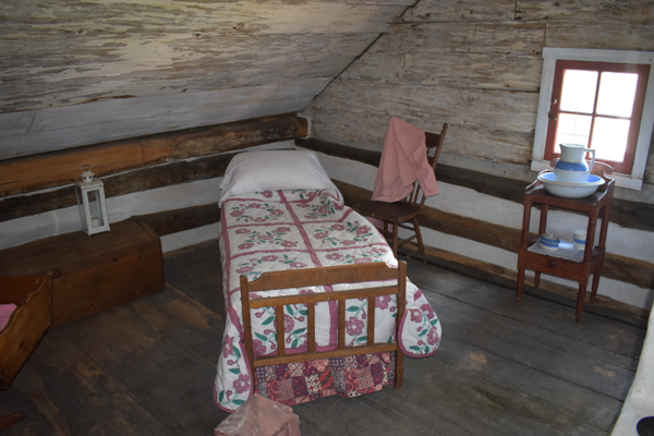 A bed and other sleeping-room items in a second-floor room of the Downingtown Log House give visitors an idea of what it would have been like to live there. (Photo by Natalie Smith)