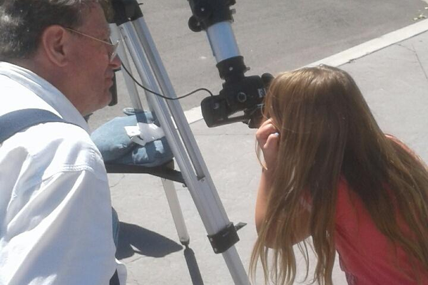 John Perry lets the public view the eclipse through his telescope. (Ruth Hendricks/City Journals)