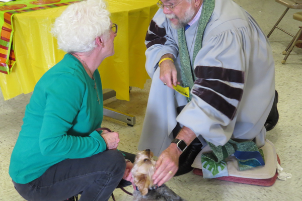 "Lucy – ""Lucy the Yorkie receives her blessing from Reverend Norman Bendroth while Lucy's human, Joanne Atkinson, looks on."" Photo Credit: Jay McFadyen"