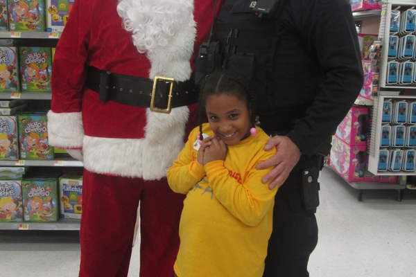 Officer Matthew Mendenhall and Khamille meet Santa in the checkout line.