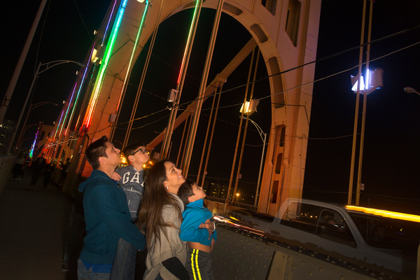 People admiring the Riverlife Energy Flow wind-powered lights on the Rachel Carson Bridge. Photo by Larry Rippel