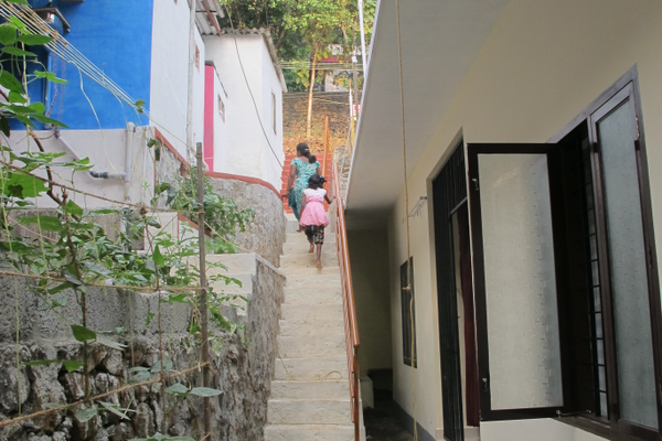 The original Snehibhavan building is on the left. The new one, completed last January, is separated by a stairway.  Both buildings are built into the hillside.  Note the climbing gourds on the wall.