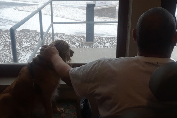 Aspen watches the snow storm with one of the residents.