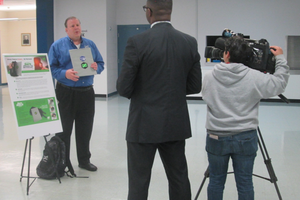 Robert Vito of Unequal Technologies is interviewed by a TV news crew on Monday.