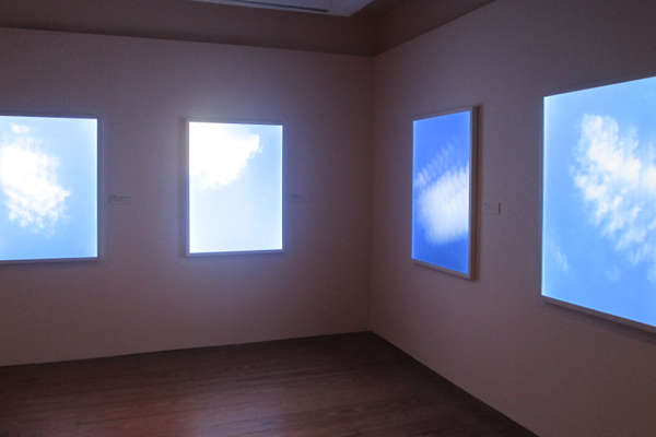 Glowing windows showing shifting clouds, by T.J. Wilcox.