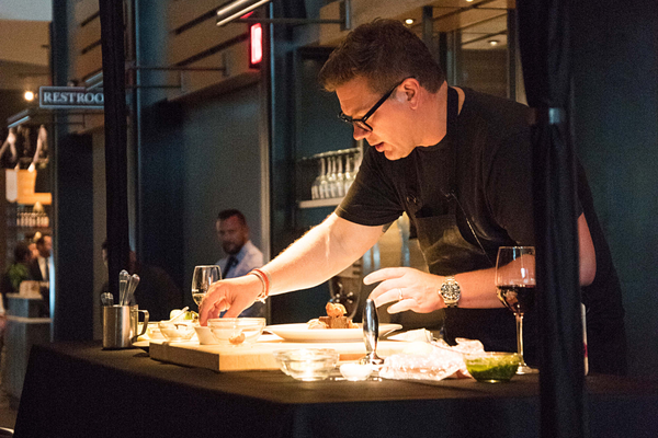 Chef Tyler Florence demonstrates how to make the main course during his visit to the Cooper's Hawk Wine Club dinner in Naples
