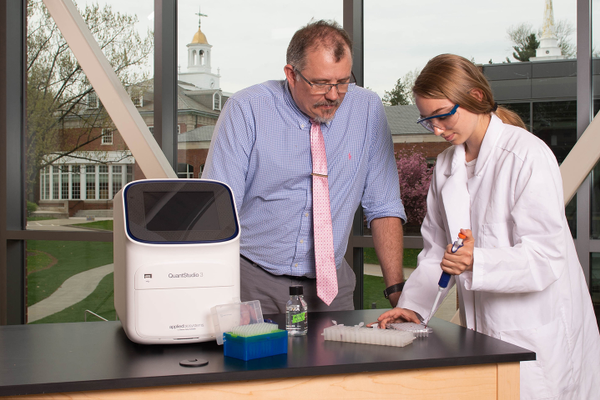 Dr. Joe Martens and an Advanced Biology student use the real-time PCR machine to observe DNA fragments being amplified and replicated.