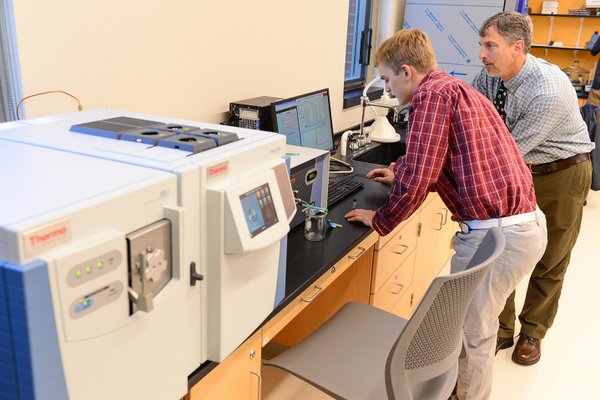 John Landreth and an Organic Chemistry student use the nuclear magnetic resonance spectrometer and gas chromatograph-mass spectrometer (GC-MS) to analyze substances.