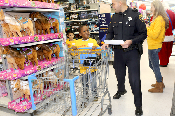 A deputy and student survey the toys at Walmart, looking for presents for relatives.