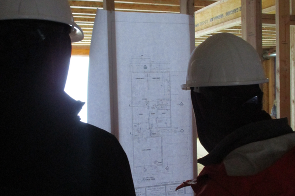 Students look at a blueprint for a home under construction.