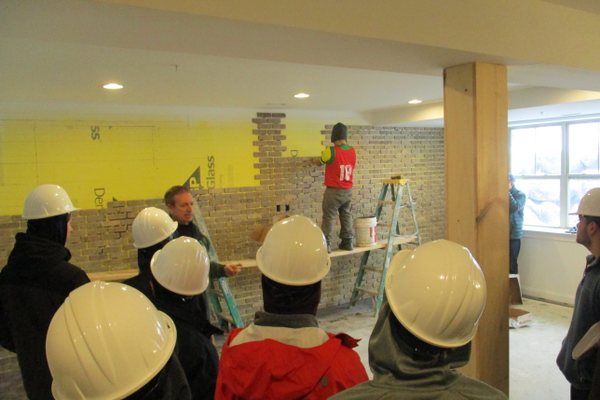 Students see stonework being installed in the lower level of one of the Stonehouse homes.
