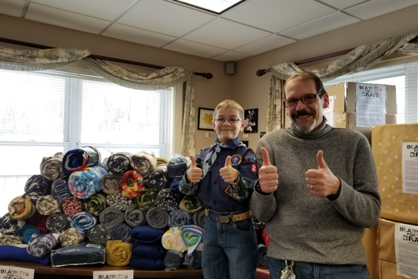 "Dracut Cub Scout P.J. Arcidiacono and Dracut Veteran's Service Agent Jeffrey Hollett are surrounded by more than 100 fleece blankets donated as part of ""Blankets for the Brave.'' Courtesy photo by Robyn Arcidiacono."