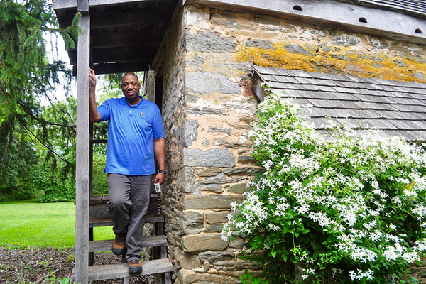 Program manager Mark Thorne pauses by a stone building at Woodlawn Manor once used to smoke meats and store food.