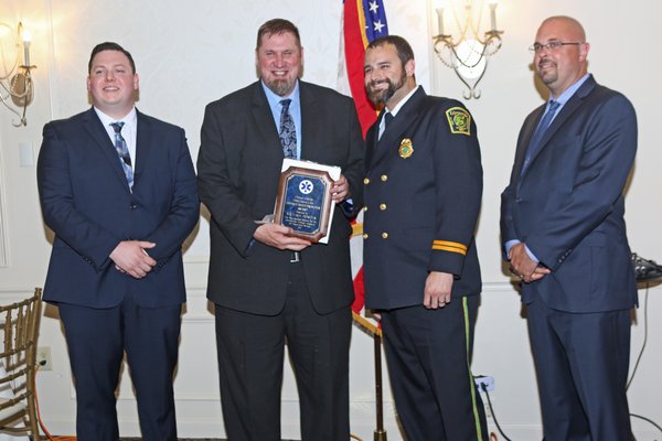 Longwood Fire Company Medic Michael Porter (second from left) receives the Advanced Life Support and Longevity Award from Longwood Fire Company EMS Captain Matt Eick (right). On the far left is Charles Brogan; on the far right is Gary Vinnacombe.