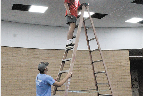 Brett Eurey (on ladder) talks with his buddy Noah Eaker about the installation of one of the new LED lights for the CHS Library.