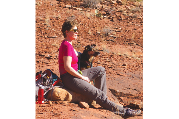 Publisher Tracy Patterson with her dog sitting in the desert resting up from a hike