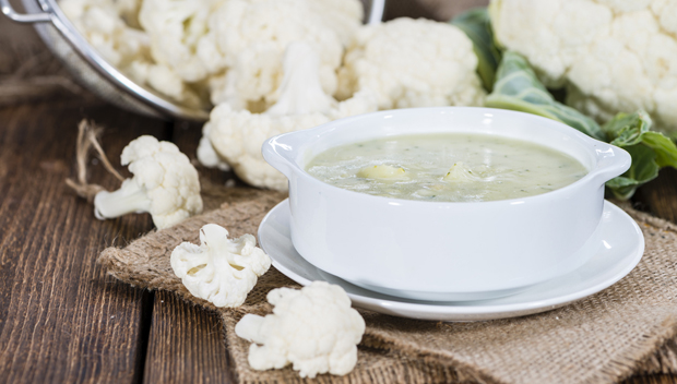 Portion of Cauliflower Soup (on rustic wooden background)