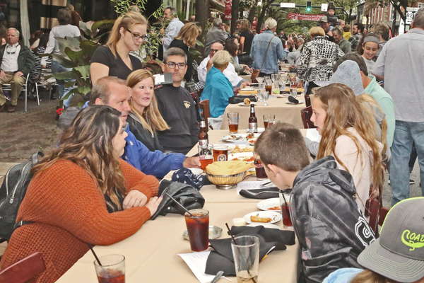 Many parade spectators added to their enjoyment by eating their dinners at tables.