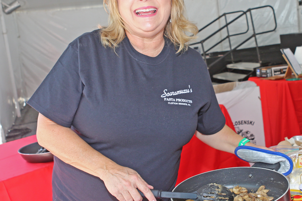 Rebecka Evans, a frequent cooking contest winner, prepares her winning pasta-and-mushroom dish at the festival
