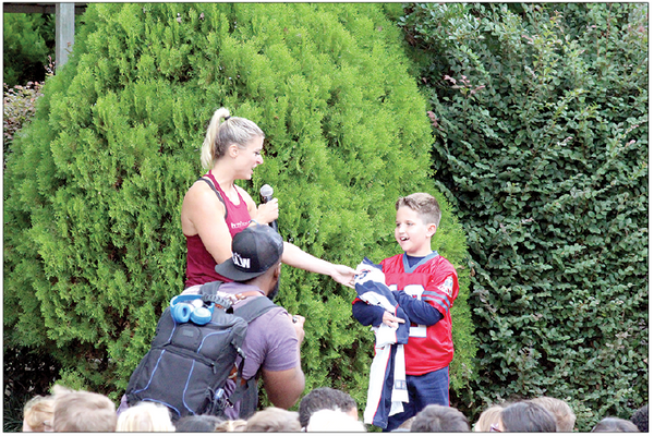 Burn Boot Camp's Lindsey Bushnell presents Braiden Brown with his very own New England Patriots football jersey. Braiden got to see the Patriots play the New York Giants on Oct. 10, in Boston, MA, as part of his Dream On 3 wish come true.