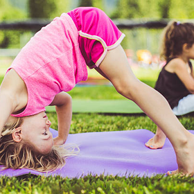 Little girls doing yoga on mats in a park picture id466329950