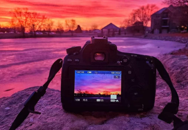 camera on rock at sunset