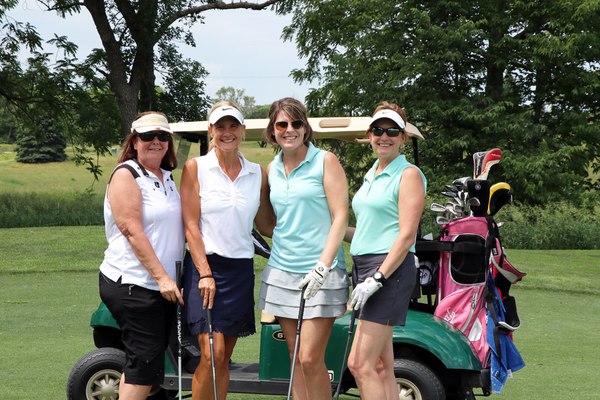 Four women standing, golf cart