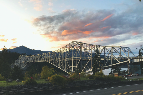 Rosy-tinged clouds float above the steel Bridge of the Gods at Cascade Locks