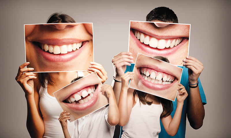 Family holding photos of smiling healthy teeth